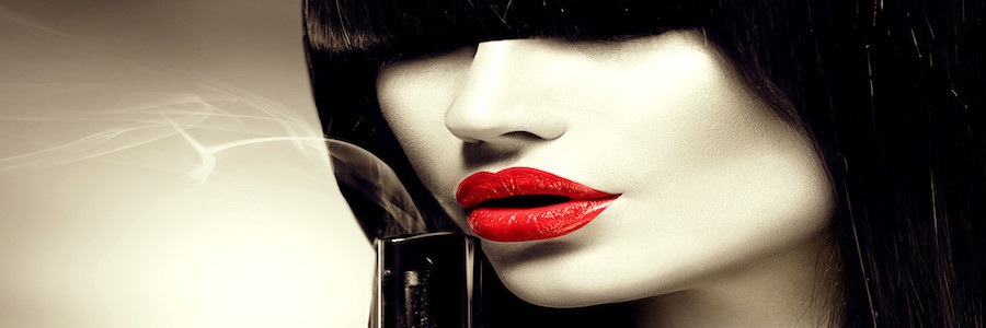 Woman with red lipstick and a smoking gun